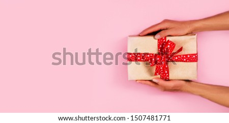 Woman hands holding wrapped craft paper box with gift and decorated with red bow on pink background. Flat lay still life for Christmas holiday, Valentine day,birthday, Mother day. Top view. Copy space #1507481771