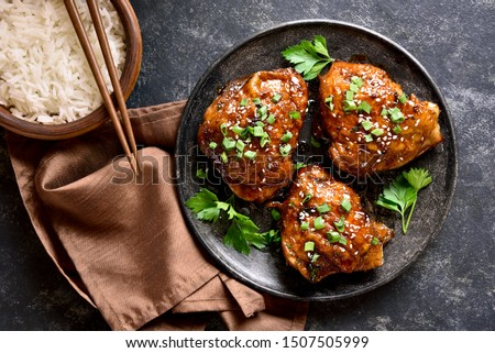 Sweet and spicy honey grilled chicken thighs and bowl of rice over dark stone background. Tasty food in asian style. Top view, flat lay #1507505999