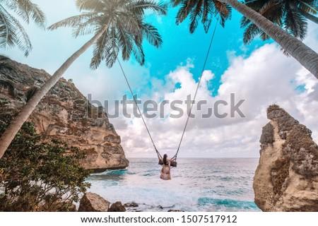 Beautiful girl on swing coconut palms on beach at Daimond  beach, Nusa Penida island Bali ,Indonesia #1507517912