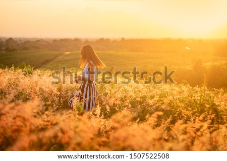 Trendy girl in stylish summer dress feeling free in the field with flowers in sunshine. Royalty-Free Stock Photo #1507522508