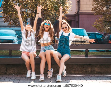 Portrait of three young beautiful smiling hipster girls in trendy summer clothes.Sexy carefree women sitting on the bench in the street.Positive models having fun in sunglasses.Raising hands #1507530440