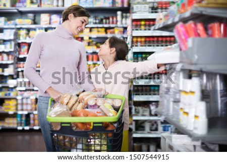 Woman with girl shopping with shopping cart in supermarket #1507544915