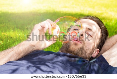 Forty years old caucasian man blowing soap bubbles while laying on grass in park during a sunny summer day #150755633