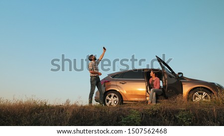 Man and woman traveling by car catches a phone signal while standing on the side of the road Royalty-Free Stock Photo #1507562468