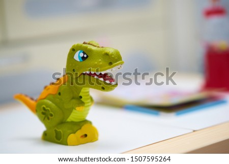 Toy dinosaur or Tyranoosaurous on table