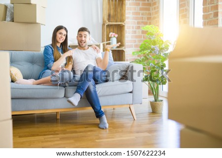 Young beautiful couple relaxing sitting on the sofa around boxes from moving to new house amazed and smiling to the camera while presenting with hand and pointing with finger. #1507622234