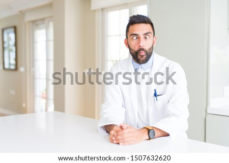 Handsome hispanic doctor or therapist man wearing medical coat at the clinic making fish face with lips, crazy and comical gesture. Funny expression. #1507632620