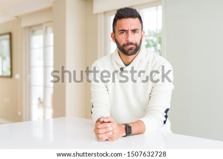 Handsome hispanic man wearing casual white sweater at home skeptic and nervous, frowning upset because of problem. Negative person. #1507632728
