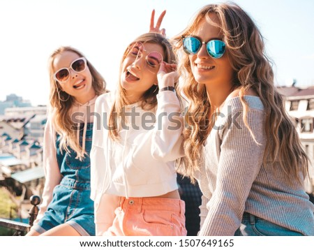 Three young beautiful smiling hipster girls in trendy summer clothes.Sexy women sitting on handrail in the street.Positive models having fun in sunglasses.They communicating and discussing something #1507649165