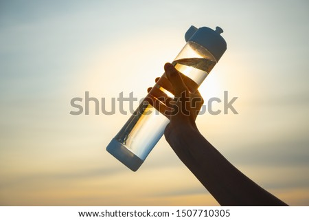 Human hand holds a water bottle against the setting sun. Close up of a reusable water bottle in a human hand, concept of thirst, rehydration and decreasing single use plastic #1507710305