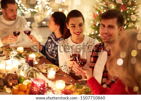 winter holidays and people concept - happy friends celebrating christmas at home feast and drinking red wine #1507710860