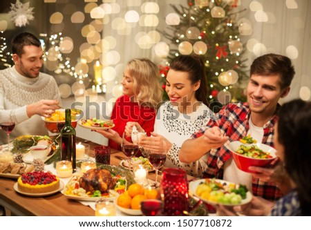 holidays and celebration concept - happy friends having christmas dinner at home and eating food #1507710872