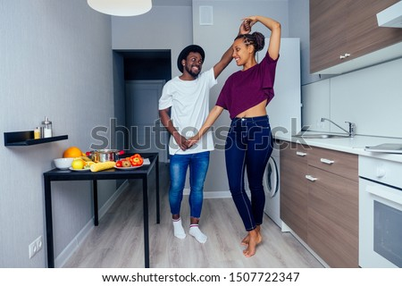Beautiful young Afro American couple is smiling while dancing in kitchen. #1507722347
