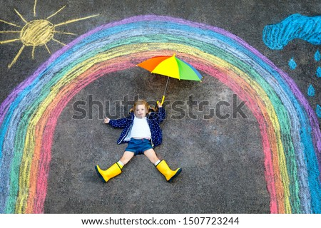Happy little toddler girl in rubber boots with rainbow sun and clouds with rain painted with colorful chalks on ground or asphalt in summer. Cute child with umbrella having fun. creative leisure