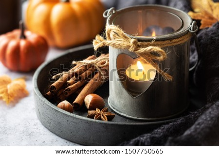 Autumn or fall concept with a romantic shabby chic lantern, aromatic spices, autumnal leaves and pumpkins at the background. Fall home decoration #1507750565