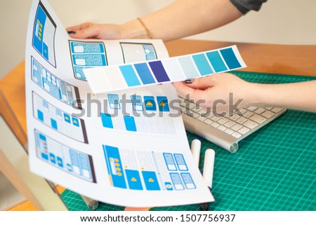 The girl picks up the color scheme for the Windows of the user program. The work of the designer of mobile applications. The color scheme of the user interface of the mobile application. UX. UI