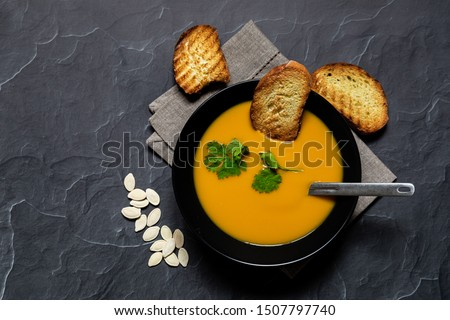 Pumpking soup served on black bowl with bread and pumpking seeds viewed from above, flatlay concept #1507797740
