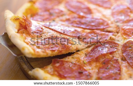 Pizza with chicken cheese and pepperoni, a piece of which is cut and laid out like a pakman, is on a wooden board and a brown background. Cheese spreads flowing streaks #1507866005
