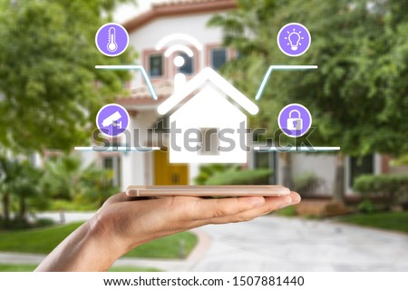 hands holding smart phone with app smart home on blurred house as backgrounds #1507881440