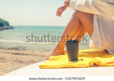 woman legs with coffee cup at car hood sea summer beach