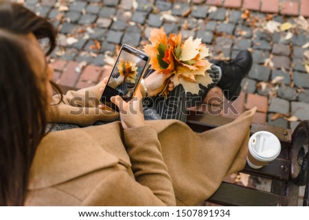 woman sitting in city park drinking coffee taking picture of bouquet of maple leaves autumn season