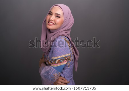 Beautiful female model wearing modern kebaya, an Asian traditional dress for Muslim woman isolated over grey background. Stylish Muslim female hijab fashion lifestyle portraiture concept. #1507913735