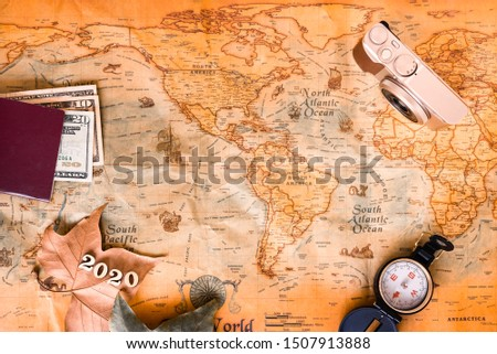 With an old background map and travel accessories, travel the world in 2020 in the holiday season. #1507913888