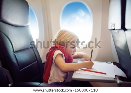 Charming kid traveling by an airplane. Joyful little boy sitting by aircraft window during the flight. Child drawing picture. Air travel with little kids