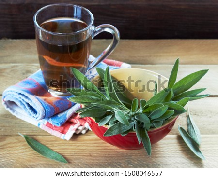 Sage herbal tea or decoction in  two glass cups with herb leaves all around on linen blue with red napkin and wooden table, closeup, copy space, alternative medicine and naturopathy concept #1508046557