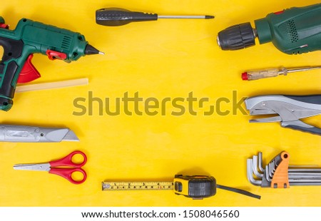 DIY Do it yourself tools on yellow background. DIY tools with copy space for text on yellow wooden background. Different tools for handwork & handmade concept. Repair concept, top view DIY theme.  #1508046560