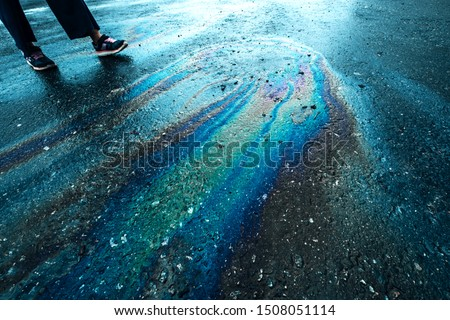 Rainbow stains on asphalt close up. Gasoline stripes, motor leaking on wet pavement concept. Man crossing through color oil slicks outdoor. Fuel spots, benzine blurs on rough surface idea #1508051114