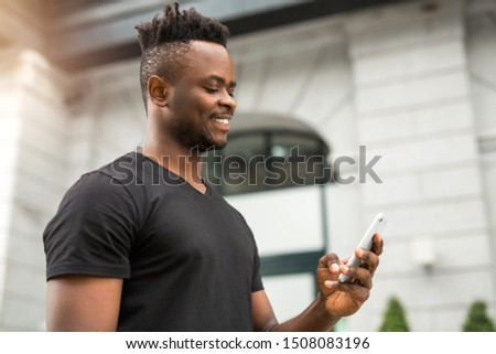 handsome young african man with a phone in his hand #1508083196