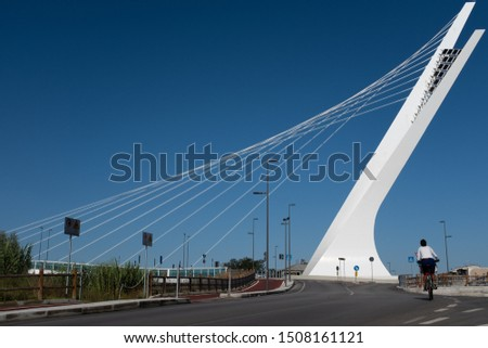 Pescara, Abruzzo/Italy 09-08-2019: a woman on a bicycle is about to cross the Ennio Flaiano bridge (design by Enzo Siviero) in the direction of the south bank of the river Aterno-Pescara. #1508161121