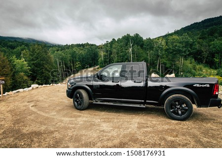 August 19th 2019. Rangely Maine USA. black 2020 Dodge Ram 1500 driving down a dirt country road in the mountains during the evening sunset using 4x4 vehicle capabilities. four wheel drive. #1508176931