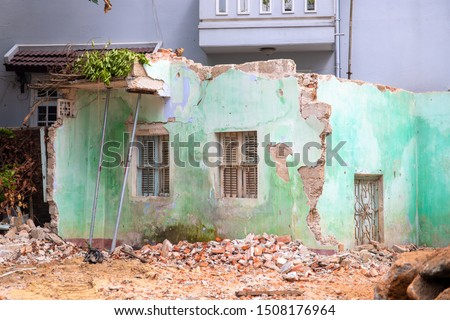 Broken house after earthquake. Old building deconstruction with new modern building on background. Deconstructive scrap salvage. Town renovation. Retro house remains with window and broken brick #1508176964