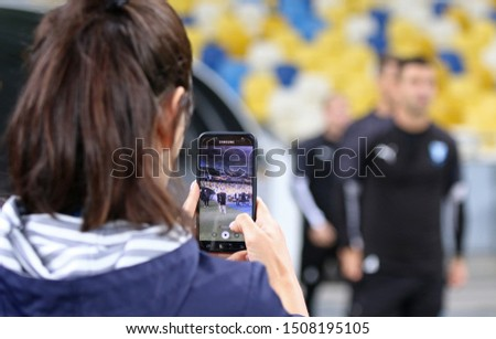 KYIV, UKRAINE - September 18, 2019: Journalist records a video on her smartphone while Malmoe players go to the pitch during the training session before UEFA Europa League game Dynamo Kyiv v Malmoe #1508195105