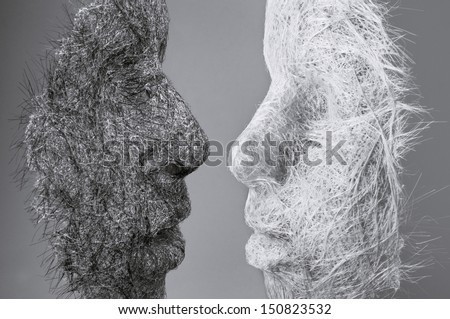 two masks made of human hair across from each other with high voltage emotions