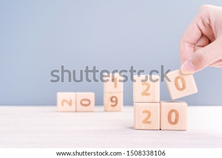 Abstract 2020 & 2019 New year countdown design concept - woman holding wood blocks cubes on wooden table and blue background, close up, copy space. #1508338106
