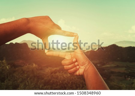 hand framing view distant over sunset. business concept