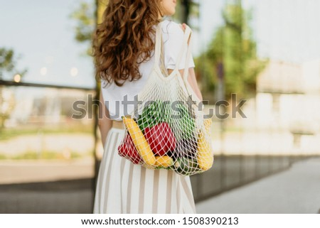 Zero waste concept with copy space. Woman holding cotton shopper and reusable mesh shopping bags with vegetables, products. Eco friendly mesh shopper. Zero waste, plastic free concept #1508390213