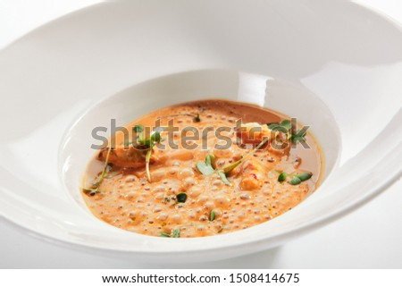 Exquisite serving airy cream bisque with seafood on white restaurant plate isolated. Smooth, creamy, highly seasoned soup based on a crustaceans broth, high cuisine molecular dish with sea food #1508414675