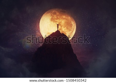 Self overcome concept as a person raising hands up on the top of a mountain over full moon night background. Conquering obstacles, success achieving. Road to win, freedom symbol. #1508450342