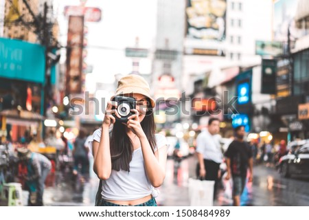 Young asian traveler happy woman in white shirt with backpack. Taking photo with instant camera beside landmark Yaowarat. Chinatown street food bokeh background. Bangkok City, Thailand #1508484989