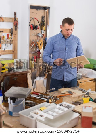 positive russian adult woodworker working  wood plank at workplace #1508492714