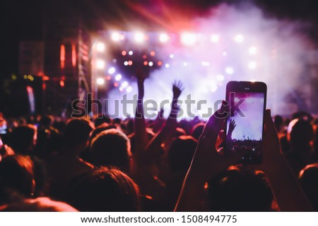People taking photographs with smart phone during a public music concert #1508494775