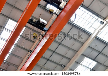 Bridge lifting Crane Hook with electric engines on the background of the industrial workshop production plant. The concept of a heavy manufacturing process at an industrial factory  #1508495786