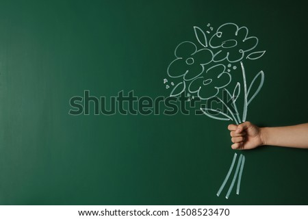 Closeup view of woman with drawn flowers on green chalkboard, space for text. Teacher's day #1508523470