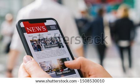 Online news on a mobile phone. Close up of businesswoman reading news or articles in a smartphone screen application. Hand holding smart device. Mockup website. Newspaper and portal on internet. #1508530010