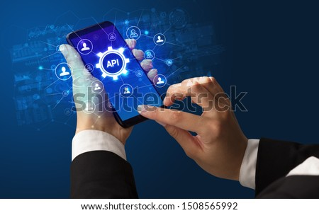 Female hand holding smartphone with API abbreviation, modern technology concept #1508565992