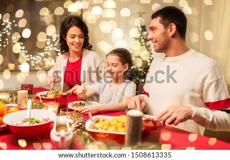 holidays, family and celebration concept - happy mother, father and little daughter having christmas dinner at home #1508613335